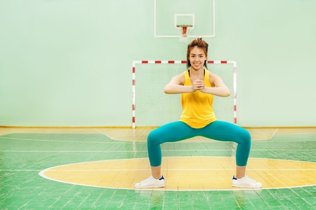 Portrait of sporty Asian girl standing in sumo squat position, working out in gymnasium
