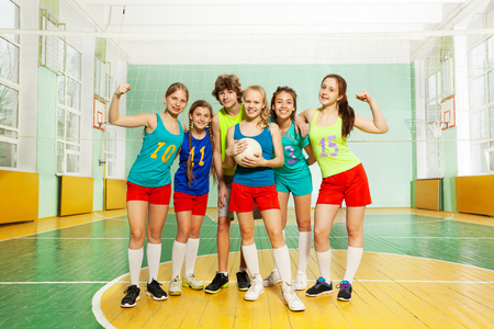 Portrait of happy teenage boys and girls, volleyball players, standing together with ball in sports hall Imagens