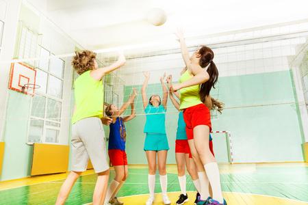 체육관에서 그물을 통해 공을 치는 십대 배구 선수의 낮은 각도보기