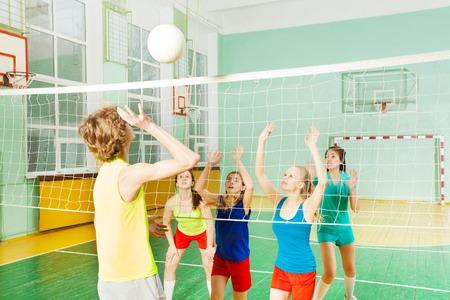 Tiener, volleybal speler, die de bal voorbij serveert