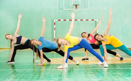 Actieve meisjes die gymnastiek in sporthal uitoefenen
