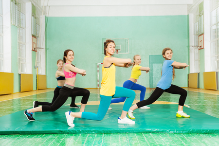 Girls making long step forward in sports hall