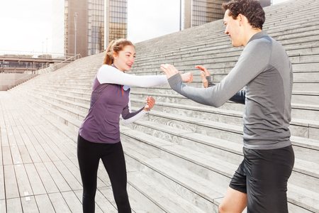 Young woman training boxing with coach outdoors