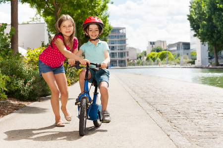 Girl teaching boy to ride bicycle on cycle path
