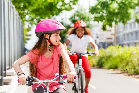 Happy girls riding bikes during summer vacation Stock Photo