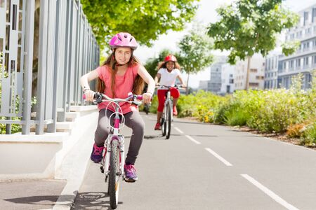 Girl riding bicycle catching up with her friend