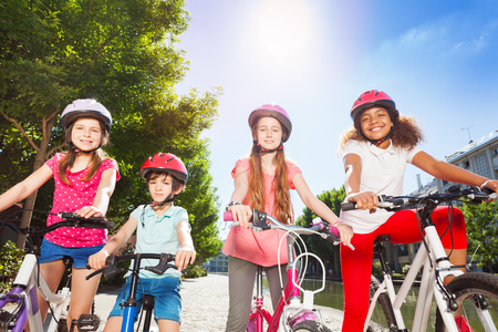Happy bike riders standing together at summer park