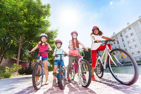 Happy children with bicycles in summer city