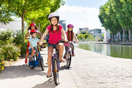 Happy girl enjoying riding bicycle on a river bank Stock Photo