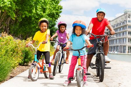 Happy African children in helmets riding bikes