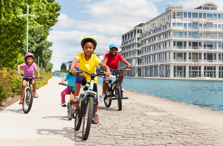 African girl cycling with friends along a river