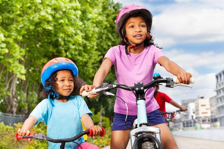Two happy African girls riding bikes in city