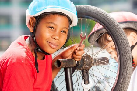 African boy repairing bicycle wheel with spanner Reklamní fotografie