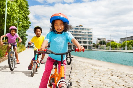 Cute African girl riding bike ahead of her friends Stock Photo