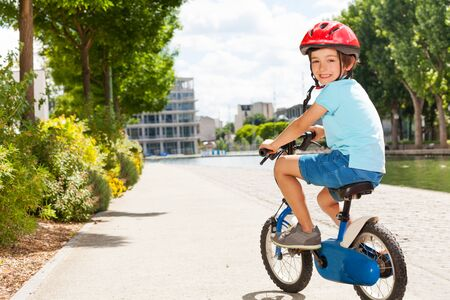 Cute little boy cycling at city park in summer