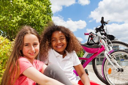 Girl friends resting after cycling in summer city