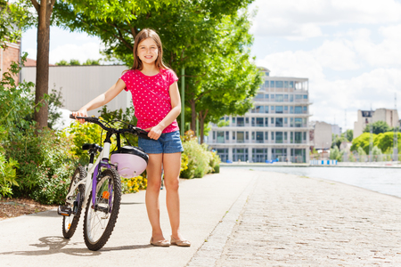 Beautiful young girl with her bicycle at city park Stock Photo