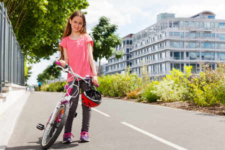 Happy girl standing with bike on cycle path Stock Photo