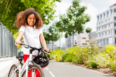 African girl standing with her bike at summer park
