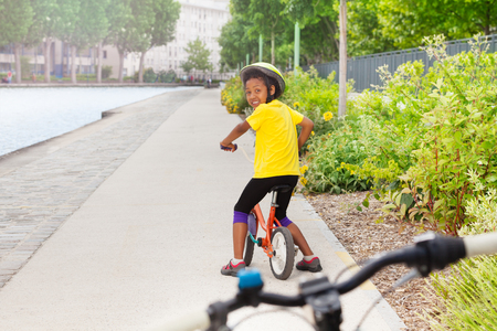 African girl riding bicycle on cycle lane in city Stock Photo