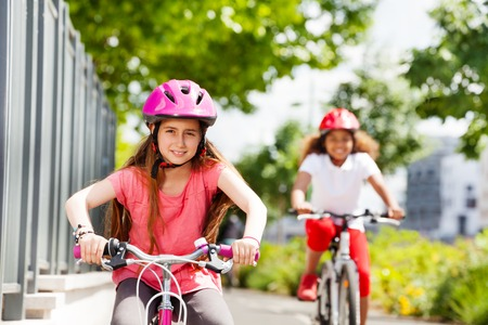 Smiling preteen girls riding bicycle in city park