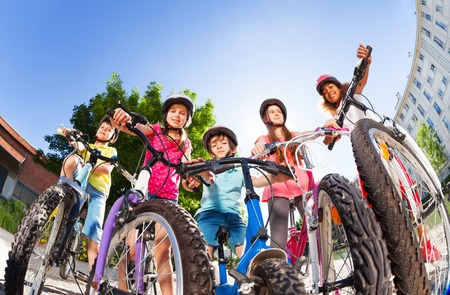 Happy little bike riders standing against blue sky Stock Photo