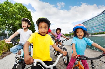 Happy children enjoying riding bicycles in summer