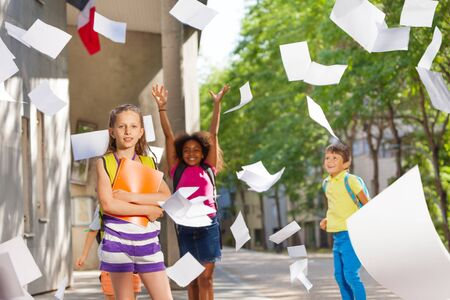Kids throw papers in the air with school on back