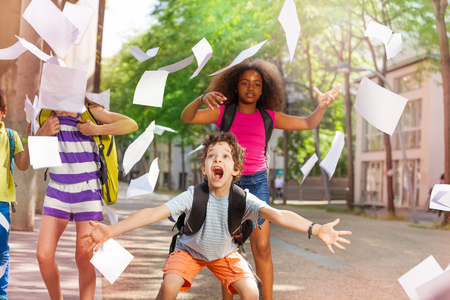 Very excited boy scream with friends throws paper Imagens - 83421425