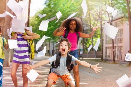 Zeer opgewonden jongen schreeuwen met vrienden gooit papier Stockfoto