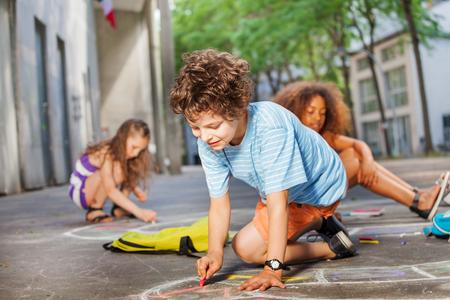 Boy draws with friends in chalk on the asphalt