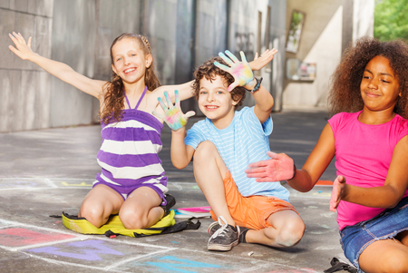 Kids drawing and showing palms in chalk