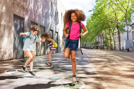 Krullend meisje met vrienden springende hinkelspel