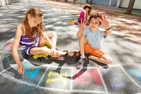 Boys and girls draw chalk on the road Stock Photo