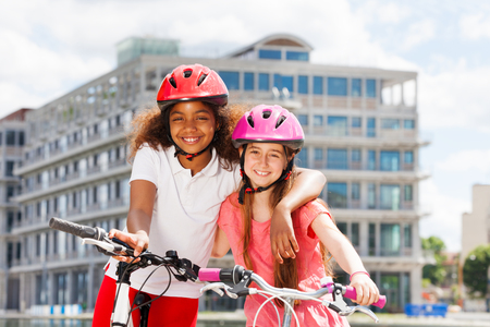 Two happy girls during bicycle ride in summer city Stock Photo