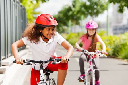 African girl racing on bicycle with her friend Stock Photo