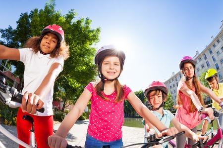Happy children riding bikes in summer city Stock Photo