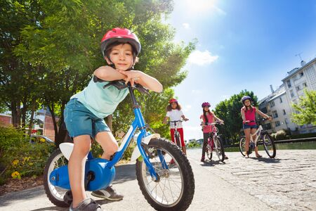 Happy little cyclist riding bike in summer city