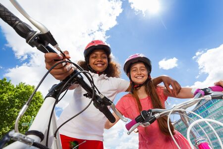 Happy girl-friends standing with their bicycles