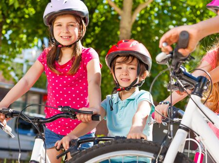 Happy little cyclists having fun at summer park Stock Photo