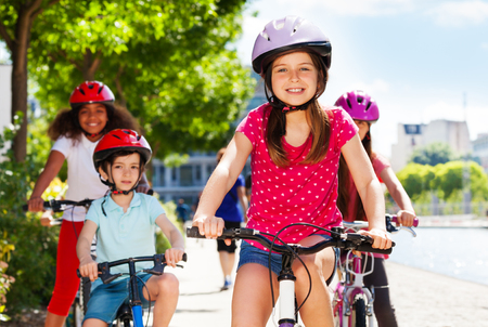 Smiling girl enjoying riding bicycle with friends