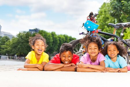 Happy children resting after cycling outdoors