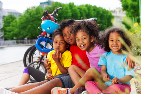Happy African children resting after cycling Stock Photo