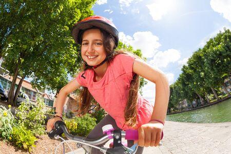 Girl riding her bike along the river embankment