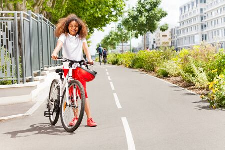 African girl standing with bicycle at city park Stock Photo