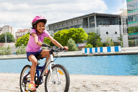 Happy African girl cycling along the river in town