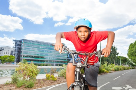 African boy riding his bike on cycle path Stock Photo