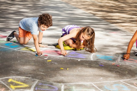 Two kids draw outside in chalk hopscotch