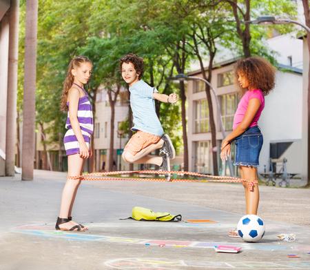 saltar: Niño, juegos, elásticos, amigos, afuera