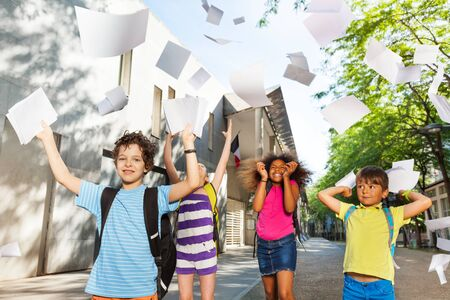 Kids throw textbook sheets in the air